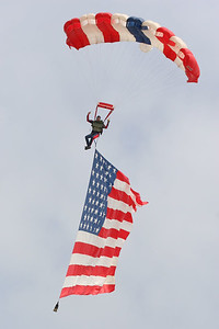 Skydiver bringing in the American flag to open the rodeo at the 2005 Ventura County Fair.
