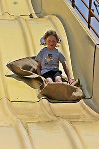 Sydney sliding down the super slide at the Seabee Days carnival