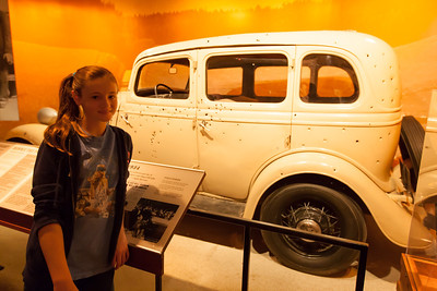 Sydney in front of Bonnie and Cylde's bullet-ridden car at the National Museum of Crime & Punishment (Image taken by Patrick R. Kane on 24 Sep 2011 with Canon EOS-1D Mark III at ISO 1600, f2.8, 1/30 sec and 19mm)