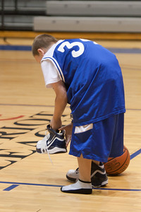 Christopher trying to put on basketball shoes as he competes against Nick during a time-out in the American University and Holy Cross women's basketball game. Christopher and Nick had to go from one end of the court to the other, getting dressed along the way in extra large shorts, a jersey and shoes, then finish with a layup. Christopher finished first and then watched the Eagles beat the Crusaders 84 to 53. (Image taken by Patrick R. Kane on 22 Jan 2011 with Canon EOS-1D Mark III at ISO 1600, f2.8, 1/320 sec and 100mm)