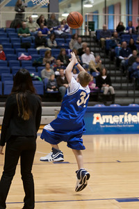 Christopher goes in for the layup while wearing an oversized jersey, shorts and shoes, and he made it on the first try! Christopher and Nick had to go from one end of the court to the other, getting dressed along the way in extra large shorts, a jersey and shoes, then finish with a layup. Christopher finished first and then watched the Eagles beat the Crusaders 84 to 53. (Image taken by Patrick R. Kane on 22 Jan 2011 with Canon EOS-1D Mark III at ISO 1600, f2.8, 1/320 sec and 75mm)