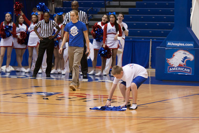 Christopher trying to pull on basketball shorts as he competes against Nick during a time-out in the American University and Holy Cross women's basketball game. Christopher and Nick had to go from one end of the court to the other, getting dressed along the way in extra large shorts, a jersey and shoes, then finish with a layup. Christopher finished first and then watched the Eagles beat the Crusaders 84 to 53. (Image taken by Patrick R. Kane on 22 Jan 2011 with Canon EOS-1D Mark III at ISO 1600, f2.8, 1/320 sec and 100mm)
