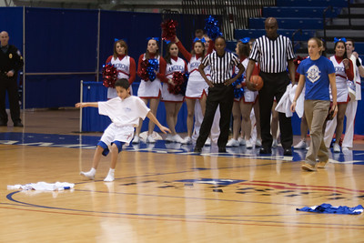 Nick competing with Christopher during a time-out in the American University and Holy Cross women's basketball game. Christopher and Nick had to go from one end of the court to the other, getting dressed along the way in extra large shorts, a jersey and shoes, then finish with a layup. Christopher finished first and then watched the Eagles beat the Crusaders 84 to 53. (Image taken by Patrick R. Kane on 22 Jan 2011 with Canon EOS-1D Mark III at ISO 1600, f2.8, 1/320 sec and 95mm)