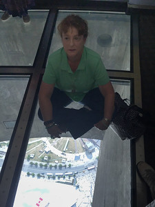 Kathy sitting on the glass floor in the observation deck of CN Tower, Toronto, Ontario, Canada (Image taken by Christopher R. Kane on Thursday, August 10, 2017 with iPhone 6 Plus at 4.15 mm, ƒ / 2.2, 1/430 sec and ISO 50)