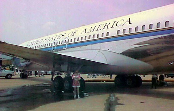 """Kathy and Sydney under the wings of the previous """"Air Force One"""" at the 1998 DOD Joint Services Open House at Andrews Air Force Base.   In 1963, this C-137 (a Boeing 707) entered service as """"Air Force One"""" with tail number 26000. It is perhaps the most widely known and historical of the presidential aircraft. Tail number 26000 is the aircraft that carried President John F. Kennedy to Dallas, November 22, 1963, and in which his body was returned to Washington, D.C., following his assassination.   In 1969, President Nixon flew in 26000 to meet the Apollo 11 crew after their trip to the moon. In 1970, National Security Advisor Henry Kissinger used 26000 to take him to Paris for secret negotiations with the North Vietnamese. Early in 1972, President Nixon flew 26000 on his historic """"journey for peace"""" to China."""