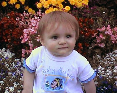 Sydney Jean Kane sitting pretty in her grandparent's backyard flower bed