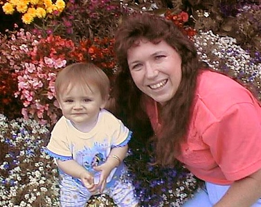 Sydney Jean Kane with Aunt Tracy sitting pretty in her grandparent's backyard flower bed.