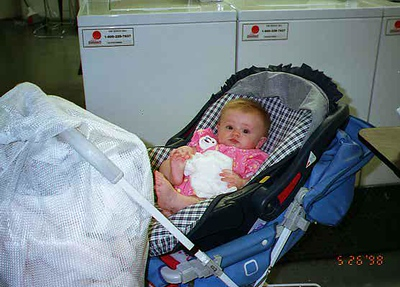 Sydney Jean Kane helping Mom out in the laundry room of the Kennedy-Warren. Notice the stroller doing double duty (i.e., baby carrier and laundry cart). We've put this thing to good use. Thanks Betsy!