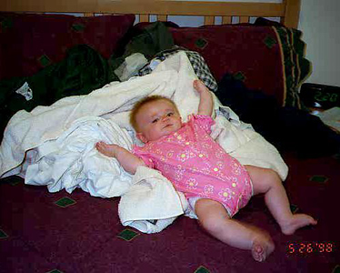 Sydney Jean Kane helping to keep the laundry from accidentally falling off the bed