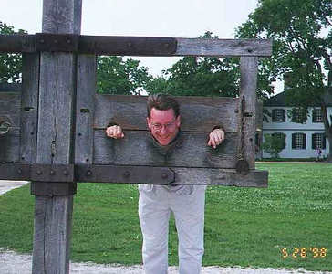 """""""I promise. I'll be good."""" Pat Kane getting to try out the stockades in Colonial Williamsburg VA."""