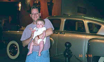 Pat and Sydney Kane in front of a Tucker sedan at the National Museum of American History. This silver Tucker sedan was built in 1948 by Preston Tucker. It is the 39th of 51 made; the Tucker never reached mass production. The engine is in the rear, and the center headlight turned right or left as the driver turned the steering wheel.