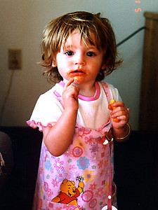 Sydney is enjoying some cheese puffs. Definitely not the tidiest of snacks.