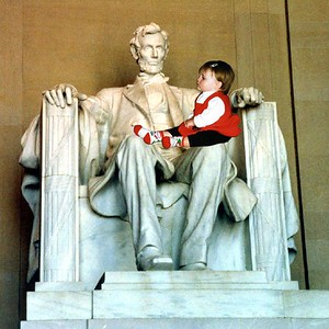 """""""Hey, what are you doing up there?!"""" Sydney Jean Kane on President Abraham Lincoln's lap at the Lincoln Memorial."""