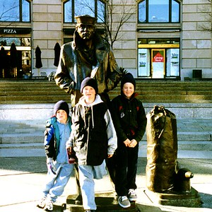 """Nathan, Ryan and Grady Roth (L to R) in front of sculptor Stanley Bleifeld's compelling Lone Sailor statue at the U.S. Navy Memorial, which is on Pennsylvania Avenue between the U.S. Capitol and the White House. Below the Memorial is Metrorail's """"Archives-Navy Memorial"""" station. We made extensive use of this (usually) efficient and clean transit system during the Roth stay."""