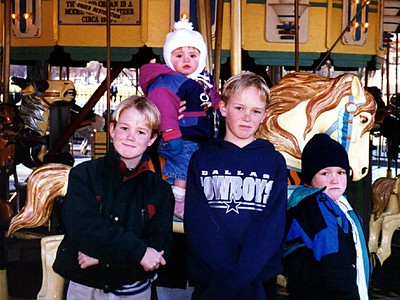 Grady, Ryan and Nathan Roth with their cousin, Sydney Jean Kane, riding the carousel on the National Mall.
