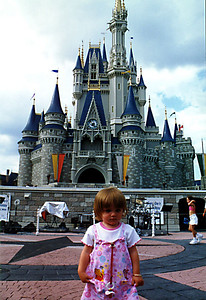 Sydney in front of the enchanted castle in the Magic Kingdom.