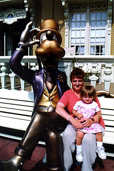 Kathy & Sydney next to Goofy's statue in the Magic Kingdom