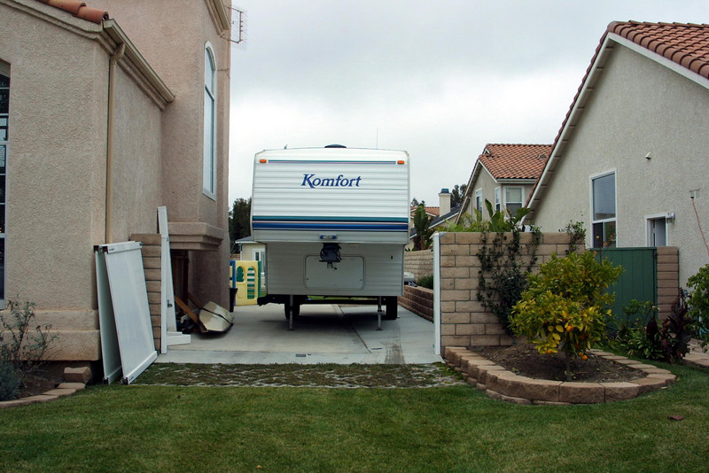 Our Komfort 23F 5th wheel trailer alongside the house. <br /> <br /> I spent a lot of long weekends in the summer of 2002 preparing the house so that we could bring our new RV home. <br /> 1. Four feet came off the concrete block wall for a little more room to navigate. I thought this would be difficult, but it was actually one of the easier parts of the job. The new gate was constructed from two vinyl fence sections (low cost and lightweight) and a removable center post that sits in a hole that we formed when the concrete was poured. <br /> 2. The first part of a French drain was next since the concrete pad would block the natural drainage out of the backyard (this part, about 70-ft from the curb to the back of the RV pad, was dug by hand). <br /> 3. It was then time for the concrete (just had to add 5-ft to the width of an existing patio), which went in pretty quickly with the help of a few friends. <br /> 4. With a trencher rented and the help of a day laborer, we excavated the remainder of the French drain and for water and electrical service (the main lines were on the opposite side of the house 150-ft away). <br /> 5. Somewhat of a diversion, but since I had the trencher for a day, we also dug lines to replace the backyard sprinkler system, which had been a mixed set of sprinklers installed by the previous owner. <br /> 6. Continuing the theme, we also ran an electrical line to just outside of the playhouse. <br /> 7. Turf-stone was laid just in front of the gate to reduce the wear and tear on the grass. <br /> 8. Raised planters were also built adjacent to the front gate and alongside the trailer.