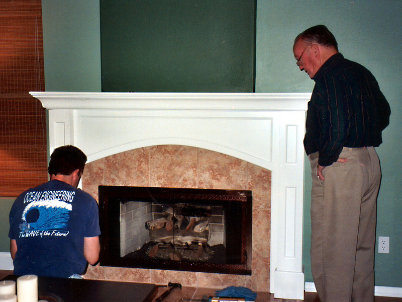 FIREPLACE. One of Kathy's makeover goals was to have a real mantel around the fireplace. The prior mantel was just a drywall bumpout (two 2x8's nailed back-to-back), which didn't provide much shelf space. Pat couldn't stand the white tile surround, so he demo'd that. Reconstruction was a team effort, with Jason from Carpets Direct doing the tile work, Barbeques Galore installing fireplace doors manufactured by FDM Co., and Pat and his dad, Grady, building the mantel. We were extremely pleased with the final product and Kathy couldn't wait to decorate it for the holiday season.