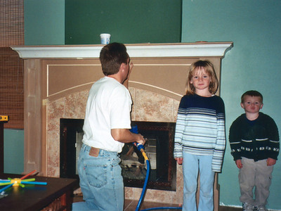 Sydney and Christopher making sure Dad keeps the mantel project on track. After the final piece of trim is nailed in place, the mantel will be disassembled and painted.
