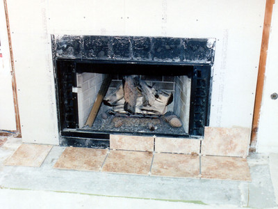 The tile is beginning to go up around the fireplace. The installer, Jason, did a great job on the surround and hearth, which had a detailed border (not yet installed).