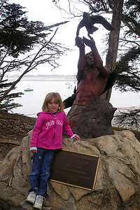 """Sydney Kane outside the Morro Bay Museum of Natural History next to Mark Greenaway's bronze sculpture, """"Seasons Come and Seasons Go,"""" which reflects life in the Morro Bay Estuary."""