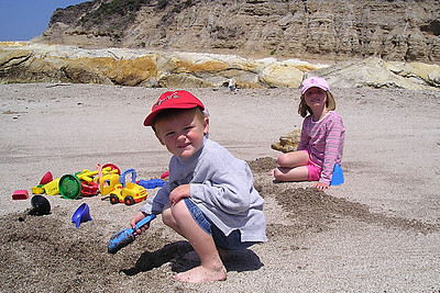 Christopher and Sydney Kane playing in the coarse sand in Corallina Cove at Montaña de Oro State Park.