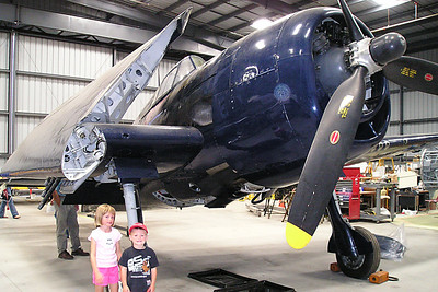 """Sydney and Christopher Kane in front of the F6F-5 #N1078Z Grumman """"Hellcat"""" Navy Fighter at the World War II Aviation Museum at Camarillo Airport. The museum is operated by the Southern California Wing of the Commerative Air Force. According to our docent, the Hellcat made a big difference when it was introduced as it was the first American plane that could """"mix it up"""" with the Japanese Zero. The museum also has a Zero on display and it is one of only a few still flying in the world."""