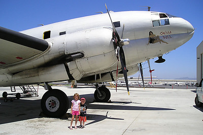 """Sydney and Christopher Kane in front of the C-46-F #N53594 Curtiss """"Commando"""" Army Air Corps transport (""""China Doll"""") at the World War II Aviation Museum at Camarillo Airport. The museum is operated by the Southern California Wing of the Commerative Air Force. From the placard inside the aircraft: The C-46 was conceived in 1936 and first flew on March 26, 1940 as a CW-20 prototype intended as a passenger plane, but due to its great load carrying ability at high altitude, it was drafted by the military as a heavy transport. Its most notable use was hauling men and material over the """"hump"""" from India-Burma to China after the Burma Road was captured by the Japanese Army. The USAF and Navy (KSC-1) continued to use the Commando in Korea, and into the mid 60's. Air America also operated the C-46 in S.E. Asia during the Vietnam era. This aircraft Ser#44-78663 was built in July 1945 at Buffalo, NY, and saw military service until 1950. As a civilian she flew as an airliner for Meteor Riddle, Zantop and Ortner Airlines. In 1978, she was donated to the CAF being assigned to the West Texas Aviation Corps, CNAC, her name then """"Humpty Dumpty."""" In 1981 she was re-assigned to the So. Calif. Wing of the CAF, who over the past several years has re-built and restored her to military configuration at a cost of over $150,000. In April of 1985, she was painted and renamed """"China Doll."""" China Doll is based at Camarillo, CA, and tours the western states teaching the history of World War II aircraft."""