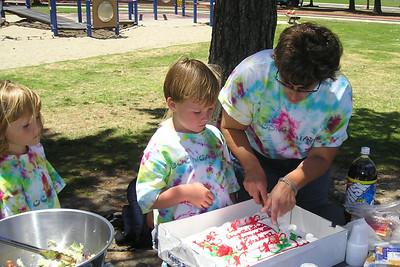 Sydney Kane watching Spencer and Ms. Liz cut their kindergarten graduation cake.