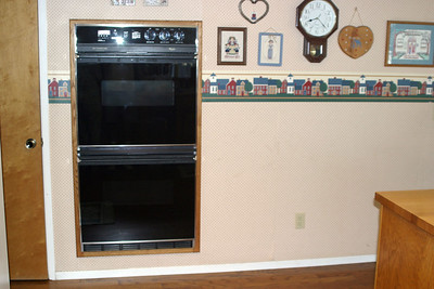 Pat's sister, Betsy, wanted to get her microwave off the countertop. There were several options available including over the range, in the center island and as a built-in to the right of the wall oven. The built-in seemed to make the most sense. This picture is just before Pat cut a hole in the wall.