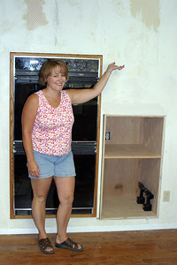 It's still a work in progress, but Betsy seems pleased already. To get to this point, Pat cut a hole in the wall so that he could climb in and put in a header to support a 2x4 stud that needed to be removed. Once that was taken care of, he cut out the opening for the cabinet, took measurements, then built the cabinet, which easily slipped into place.