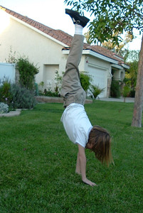 Sydney Kane in the middle of a cartwheel at home.