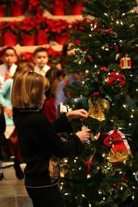Sydney decorating the Christmas tree during St. John's Christmas Program