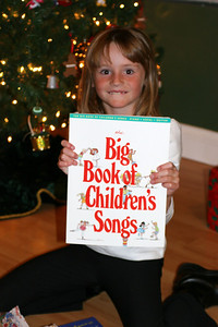 """Sydney was extremely excited once she opened the """"The Big Book of Children's Songs,"""" which she'll get to learn to play on the piano."""