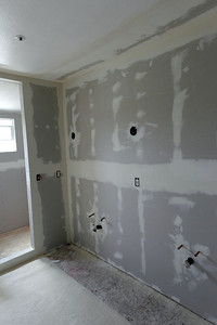 The master bath is starting to come back together, with the rotted floor replaced and the drywall installed. The shower is also being boxed in with a partition wall next to the vanity and a sloped ceiling that is required for steam showers.