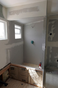 The master bath is starting to come back together, with the rotted floor replaced and the drywall installed. The shower is also being boxed in with a partition wall next to the vanity and a sloped ceiling that is required for steam showers. I've used sheetrock in the shower because I will be using a Kerdi membrane for waterproofing.