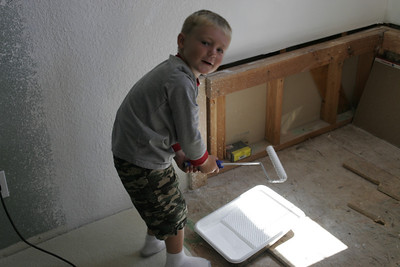 Christopher applying primer over the drywall texture in the master bath.