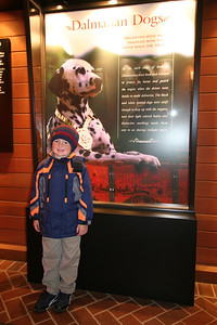 """This sign next to Christopher in the Clydesdale Hamlet at the Anheuser-Busch brewery in Fort Collins reads: """"Dalmation Dogs have traveled with the hitch since the 1950s. In the early days of brewing, Dalmations were bred and trained to protect the horses and guard the wagon when the driver went inside to make deliveries. The black and white spotted dogs were swift enough to keep up with the wagons, and their light colored bodies and distinctive marking made them easy to see during twilight hours."""""""