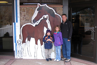 Pat, Sydney and Christopher seeing how they measure up to a Clydesdale at the Anheuser-Busch brewery in Fort Collins.