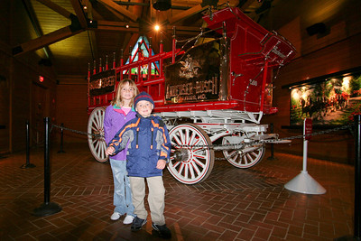 Sydney and Christopher in front of a Budweiser beer wagon in the Clydesdale Hamlet at the Anheuser-Busch brewery in Fort Collins.
