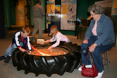 Grandma supervising Christopher and Sydney as they dig for dinosaur bones in an exhibit at the Fort Collins Museum.