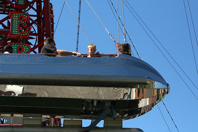 """Pat and Christopher enjoying a ride aboard the Golden Zephyr at Disney's California Adventure Park. These stainless steel silver bullet rockets glisten in the California sun as they take you for a spin at the water's edge. Orbit suspended from a 90-foot tower in """"galactic gondolas"""" that were inspired by Buck Rogers and Flash Gordon."""