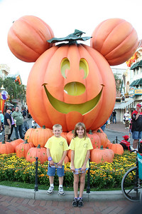 Christopher and Sydney in front of the giant Mickey pumpkin in Disneyland