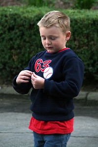 Christopher playing with little berries to throw at his sister and dad after a long day at the Los Angeles Zoo.