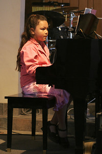 Alanna playing the piano during her recital