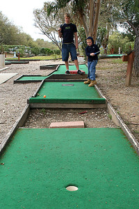 Christopher, with Grady looking on, playing a round of miniature golf while visiting the Roth Lake House, which is located on Lake Nacimiento in the Oak Shores gated community. To get from one carpet to the other, you're supposed to bounce the ball off of the brick in the middle.