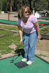 Betsy playing a round of miniature golf while visiting the Roth Lake House, which is located on Lake Nacimiento in the Oak Shores gated community.