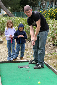 Ryan, with Sydney and Christopher looking on, playing a round of miniature golf while visiting the Roth Lake House, which is located on Lake Nacimiento in the Oak Shores gated community.