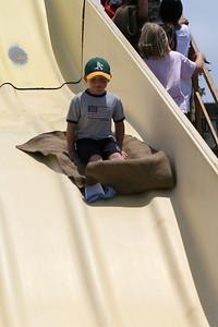 Christopher sliding down the super slide at the Seabee Days carnival
